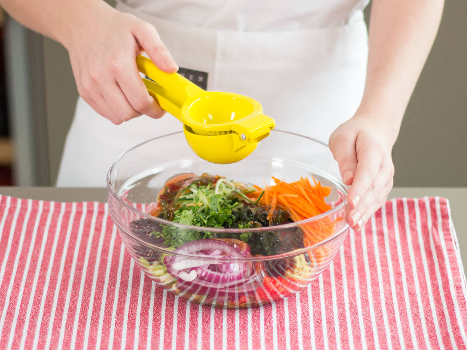 Algen, Karotte, Gurke, Zwiebel, Chili, Frühlingszwiebeln und Koriander in einer großen Schüssel vermengen. Ingwer in die Schüssel reiben. Sesamöl, dunklen Sesam, süße Chilisoße und Limettensaft hinzugeben. Nach Geschmack mit Salz und Pfeffer würzen. Den Salat anschließend gründlich mischen.