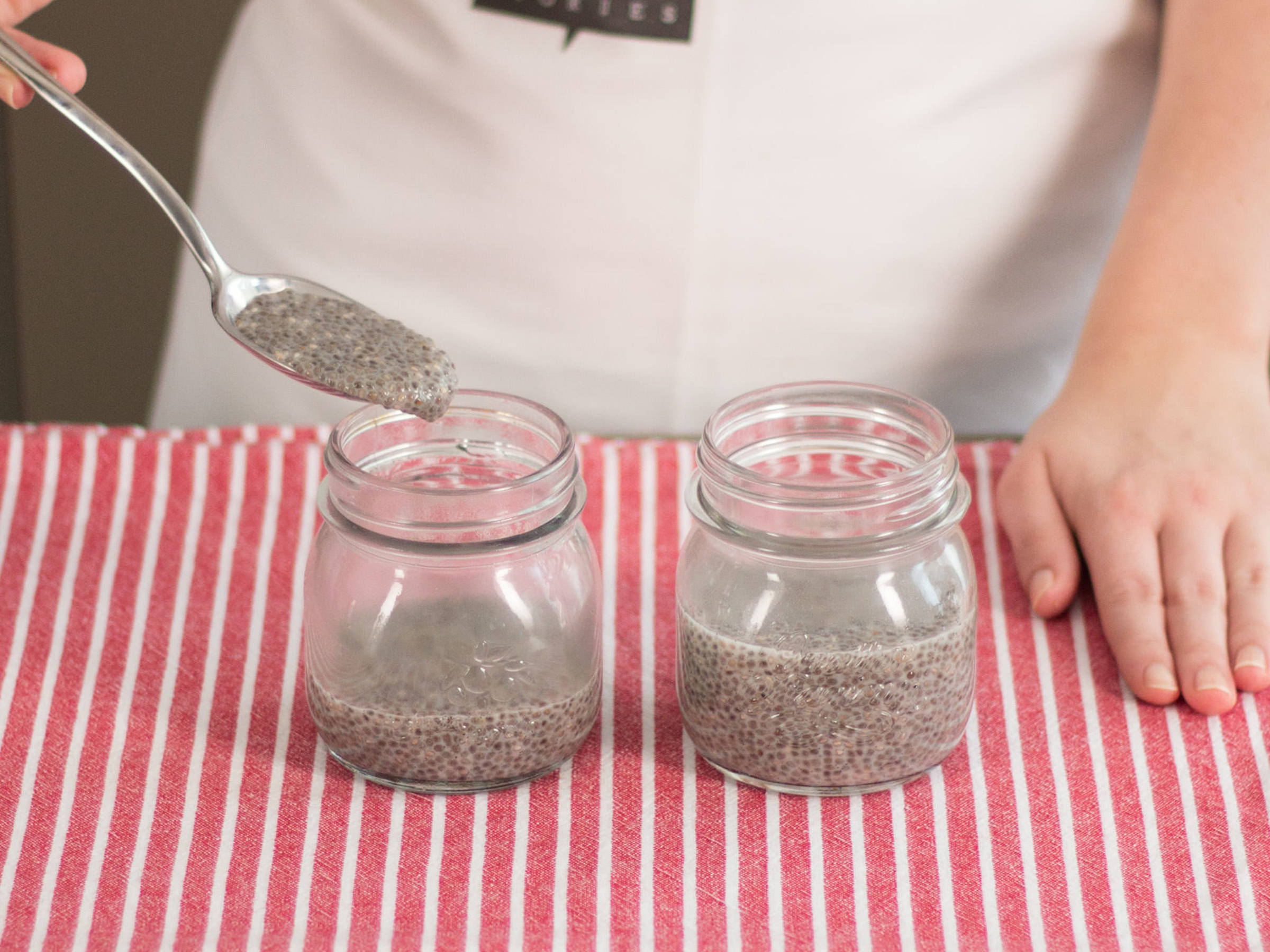 Spoon chia pudding into jars for serving.