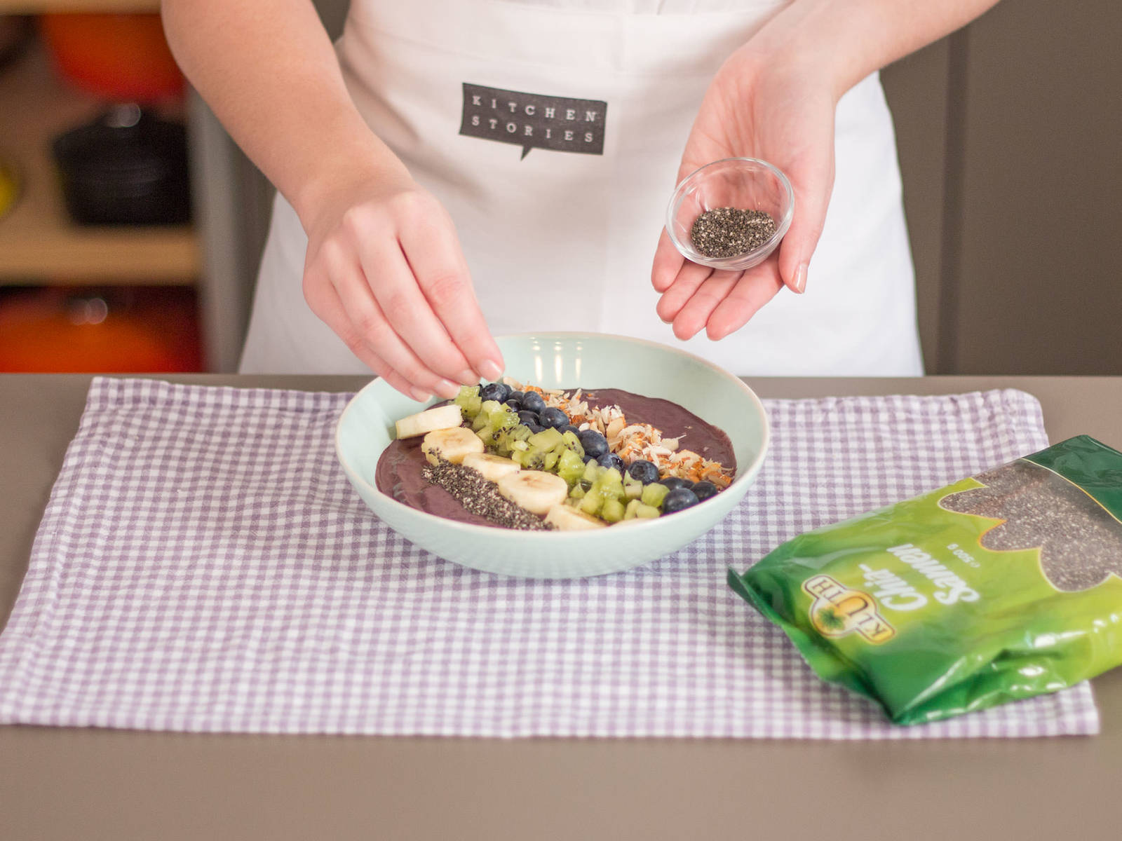 上一步中制好的巴西莓果酱倒入碗中。饰以香蕉、奇异果、蓝莓、杏仁和奇亚籽。 这款饮品既可作为补充能量的早餐,也可作为下午的提神饮料,尽情享用吧!
