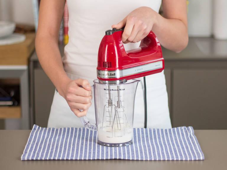 Eine Kaffeetasse oder ein Glas mit heißem Wasser auffüllen. In einem Messbecher Sahne leicht anschlagen, sodass sie gerade cremig ist.