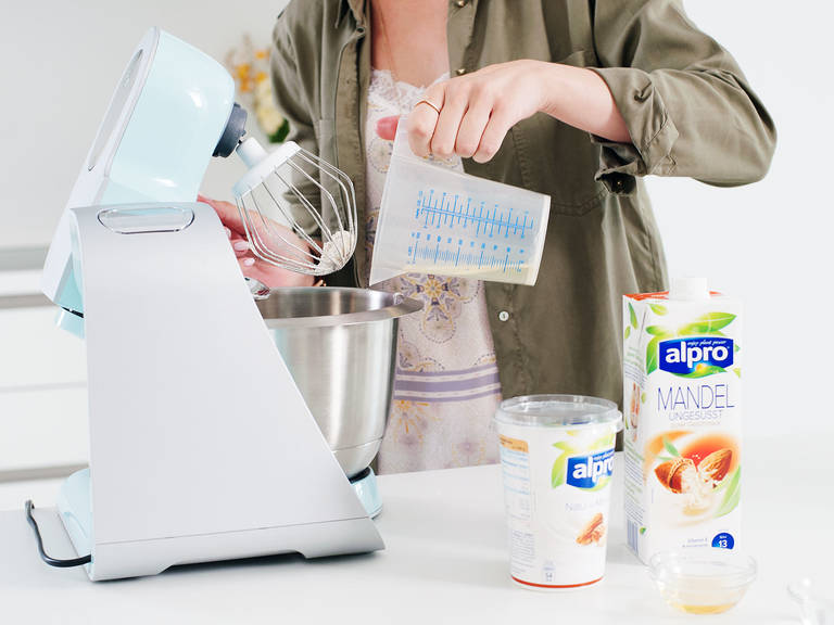 Preheat oven to 200°C/400°F. Combine some of the rosewater, flour, ground almonds, baking powder, salt, sugar, some of the yogurt, oil, vinegar, and almond drink in the bowl of a stand mixer.