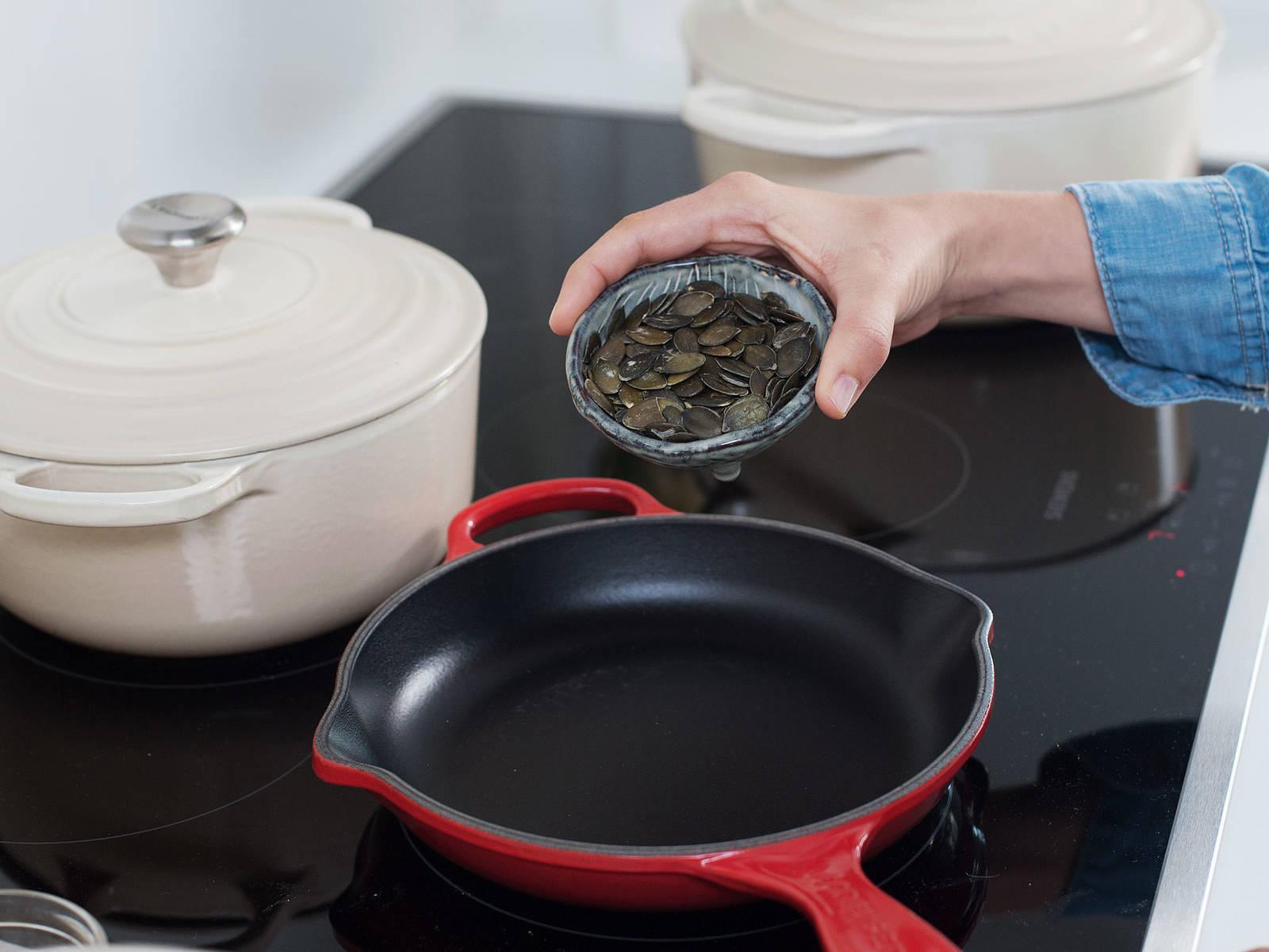 在无油的大煎锅中,中火烘烤南瓜籽1-2分钟,直至发出香气。关火取下,置于一旁备用。