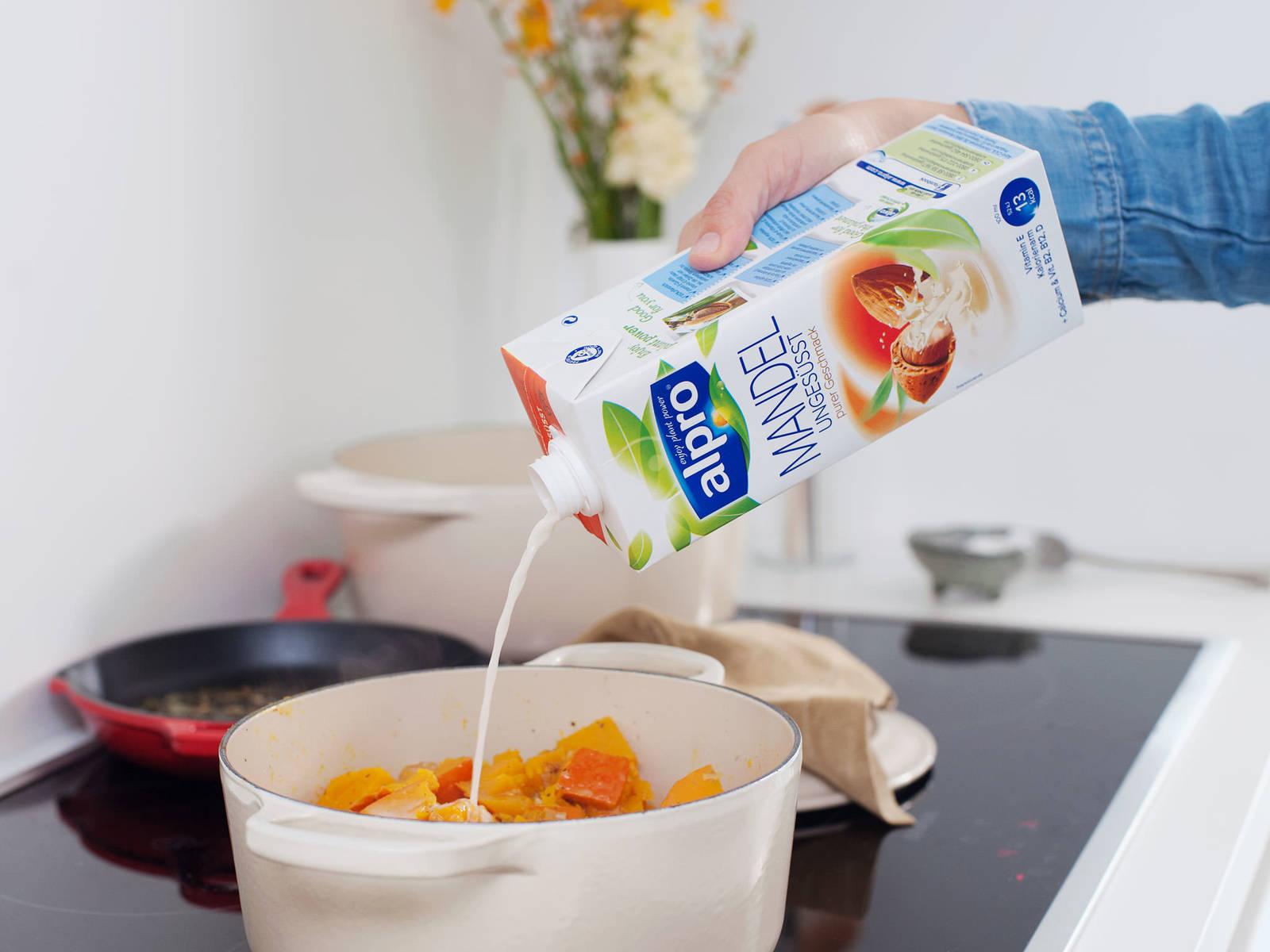 调至中火,放入蒜末和干香料,翻炒1-2分钟。倒水,盖上盖子,煮上5-7分钟,直至南瓜变软。与此同时,煮沸一大锅水;加盐。放入意面,根据包装说明煮至有弹牙嚼劲。南瓜煮好后,倒入杏仁茶和腰果泥。彻底翻动,再煮1-2分钟。