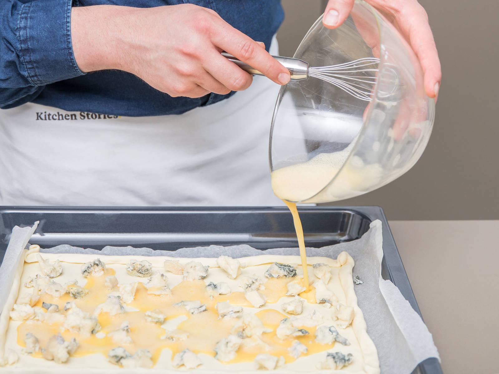 Backofen auf 180°C vorheizen. Blätterteig mit Backpapier auf ein Blech legen (Kanten umschlagen, damit ein Rand entsteht). Eine dünne Schicht Gorgonzolakäse darauf verteilen. Die Eier schlagen und auf die Käseschicht verteilen.