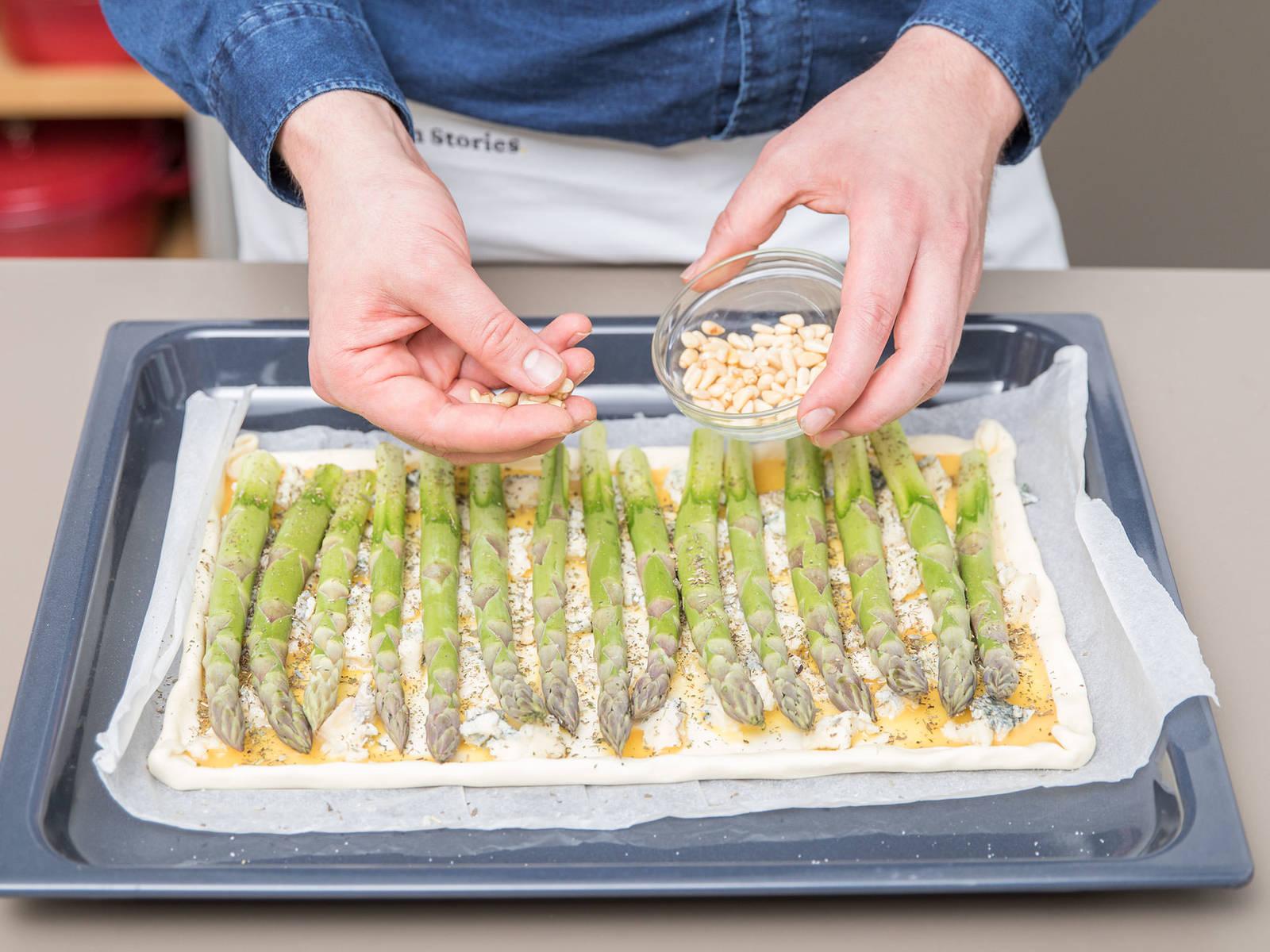 Spargel vorbereiten und Knoblauch hacken. Spargelstangen auf die Eimasse legen. Mit Pinienkernen, Knoblauch, Kräutern, Salz und Pfeffer bestreuen. Bei 180°C etwa 20 Min. goldbraun backen.