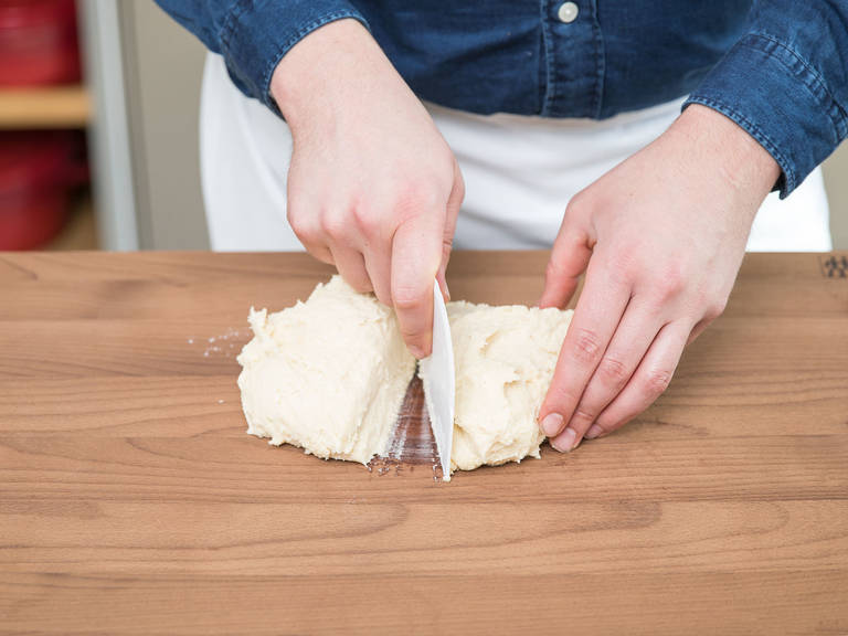 Wasser hinzugeben. Zu einem glatten Teig verkneten. Den Teig teilen und zu flachen Scheiben formen. Die beiden Scheiben in Frischhaltefolie einwickeln und ca. 60 Min. lang in den Kühlschrank legen.