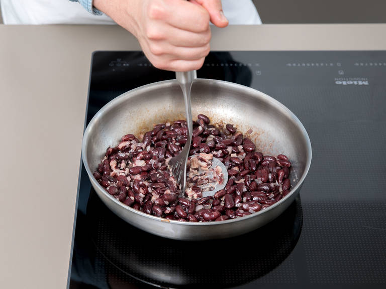 Next, we will make the beans. Cut the onion. Drain and rinse the beans, heat some oil in a pan, fry the onion, then add the beans and mash them in the pan, or leave them whole because they will still taste great.
