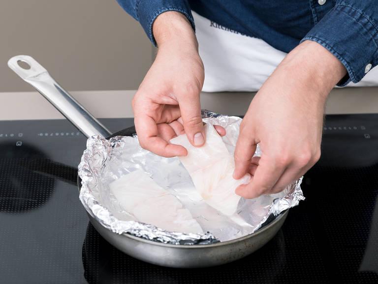 Mehrere Schichten Aluminiumfolie in der Größe der Pfanne zuschneiden und Löcher hineinstechen. Mehrere Schichten der Folie in die Pfanne legen, damit die Folie später, wenn sie hochgehoben wird, nicht auseinander fällt. Wasser zum Kochen bringen und in die Pfanne geben. Das Wasser sollte hoch genug sein um die Filets komplett zu bedecken. Wolfsbarschfilet ca. 2 Min. pochieren, oder bis er gar ist.