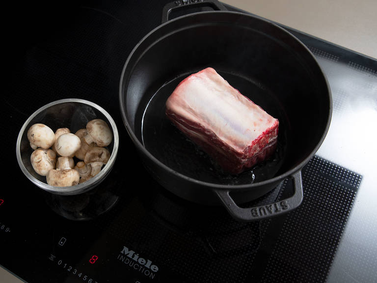 Peel and thinly slice garlic. Season short ribs with salt and pepper. Heat oil in a pot over medium-high heat and sear meat on both sides, then add garlic.