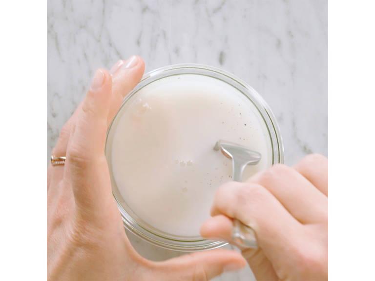 Vanilleschote der Länge nach aufschneiden und Mark auskratzen. Das Mark mit dem Kokosnussdrink, dem Mandeldrink und dem Honig in ein Glas geben. Die Mischung gut verquirlen.