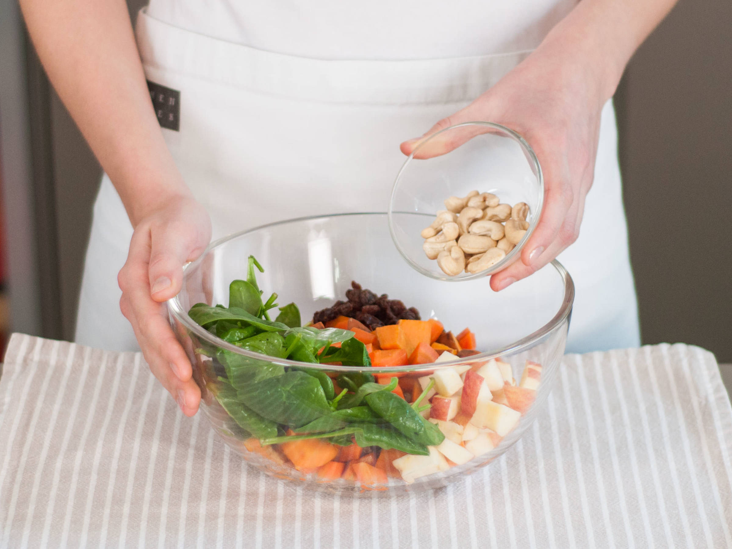 In a large bowl, combine sweet potato, apple, carrot, spinach, raisins, and cashews. Mix well to combine.