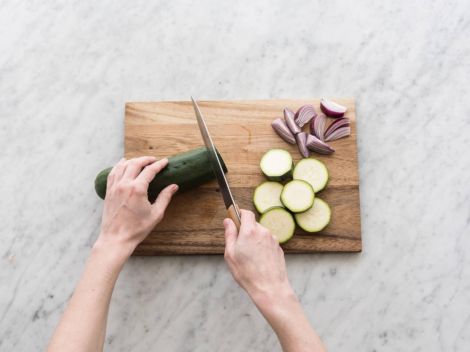 洋葱去皮后对半切成四份。葱横切成片,西葫芦切成圆片。在大碗中放入西葫芦、洋葱,与橄榄油、盐和胡椒混合。