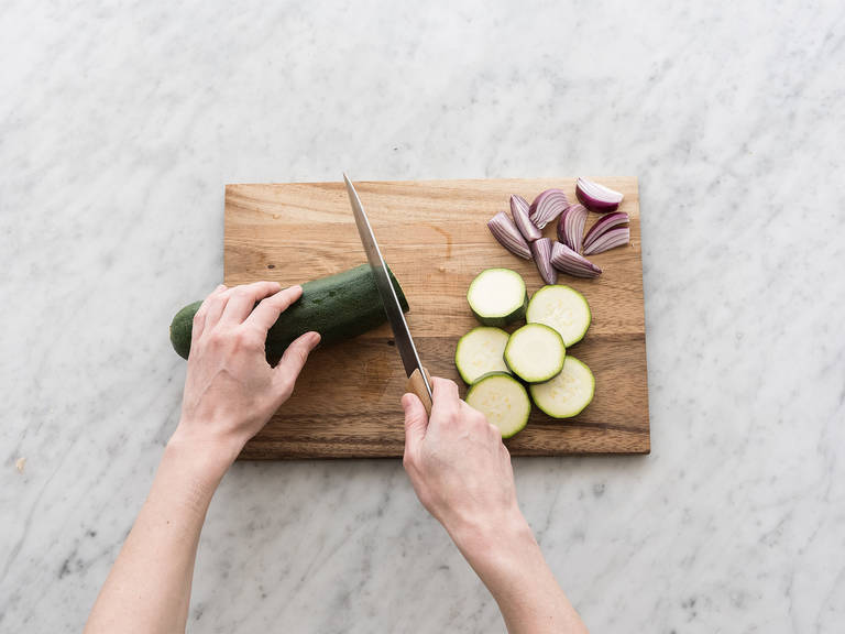 Peel onion, cut in half, and then cut halves into quarters. Cut green onion crosswise into slices and zucchini into medallion-sized pieces. In a large bowl, toss zucchini and onion with olive oil, salt, and pepper.