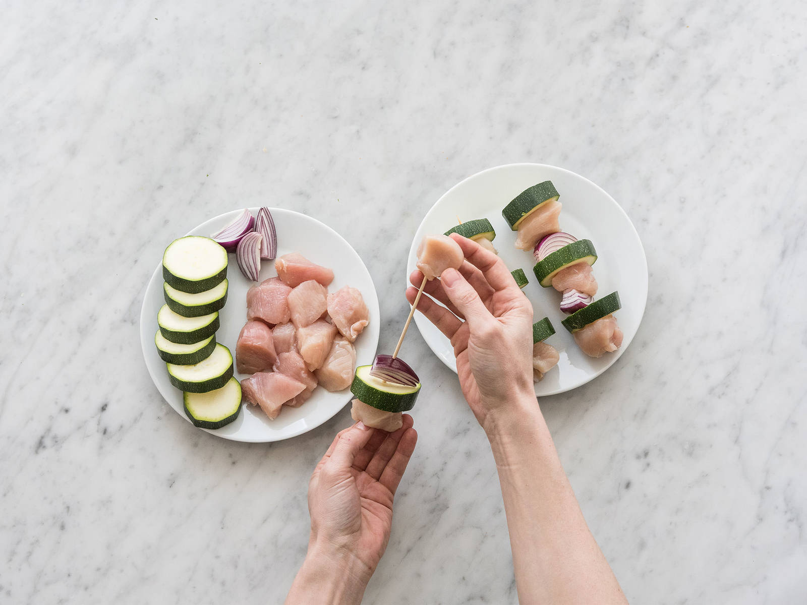 Preheat oven to 200°C/390°F. Thread chicken, zucchini, and red onion onto wooden skewers. In a large frying pan, heat up olive oil over medium heat and sauté skewers for approx. 2 – 3 min. per side. Then, place on a parchment paper-lined baking sheet and place in preheated oven at 200°C/390°F and bake for approx. 10 – 12 min.