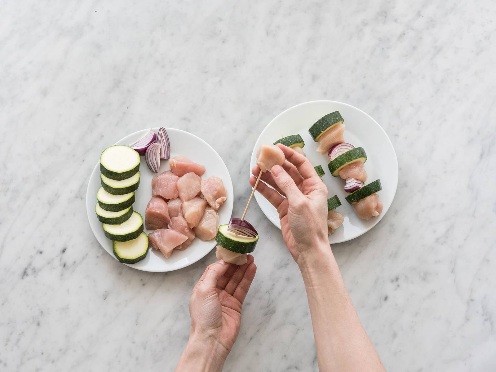 将烤箱预热至200度。用木串将鸡肉、西葫芦和红洋葱串起来。在大煎锅中中火加热橄榄油,煎制鸡肉鲜蔬串,每面2-3分钟。然后将其放到铺好烘焙纸的烤盘上,在预热好的烤箱中以200度烤制10-12分钟。