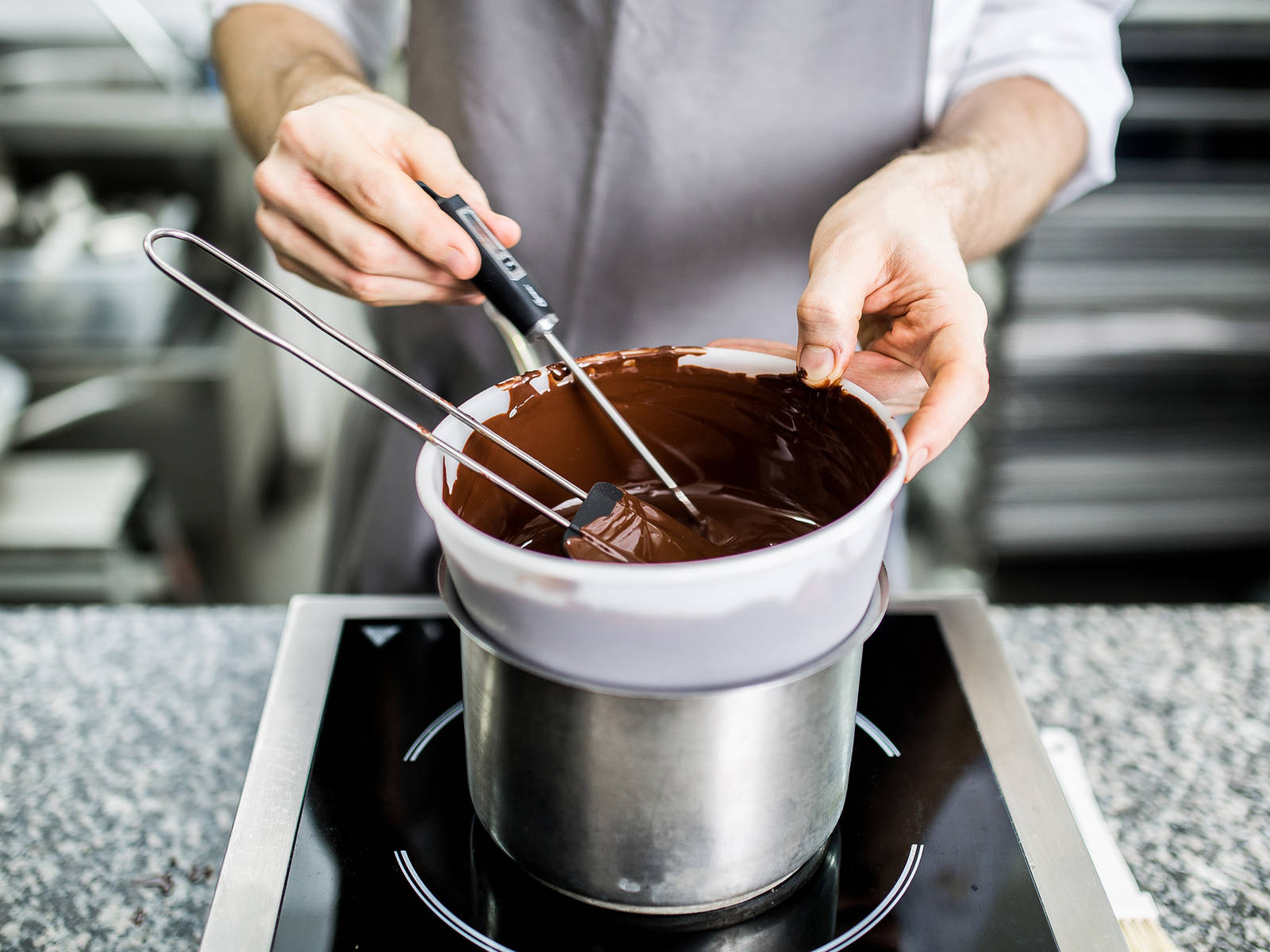 Set up a double-boiler by placing a heatproof bowl over a small pot of simmering water. Place half of the chocolate in the heatproof bowl and melt. Take off heat once it has reached 50°C/122°F. Set aside. Add rest of chocolate and gently stir.