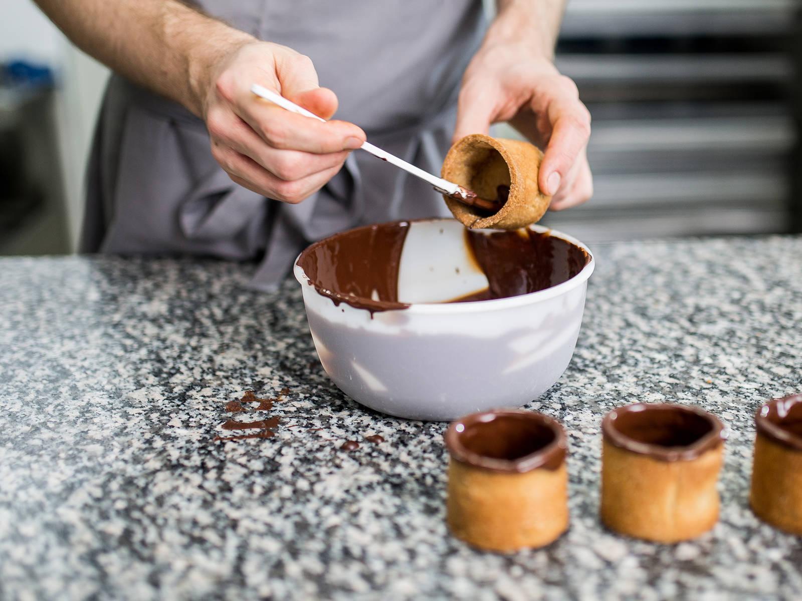 一旦巧克力混合物温度达到32摄氏度,便马上用油刷沾取巧克力酱,刷涂在曲奇杯内壁和杯底。为了确保杯子不漏,在杯内刷上两层巧克力酱。为了确保杯口也不漏,将杯口朝下,蘸进巧克力酱,再正面朝上,让多余的巧克力自然滴落。如果喜欢,可以在此步骤加上杏仁碎或彩色巧克力用作装饰,或者等到巧克力重新冷却后撒上金箔。将曲奇杯放入冰箱冷藏约20分钟。