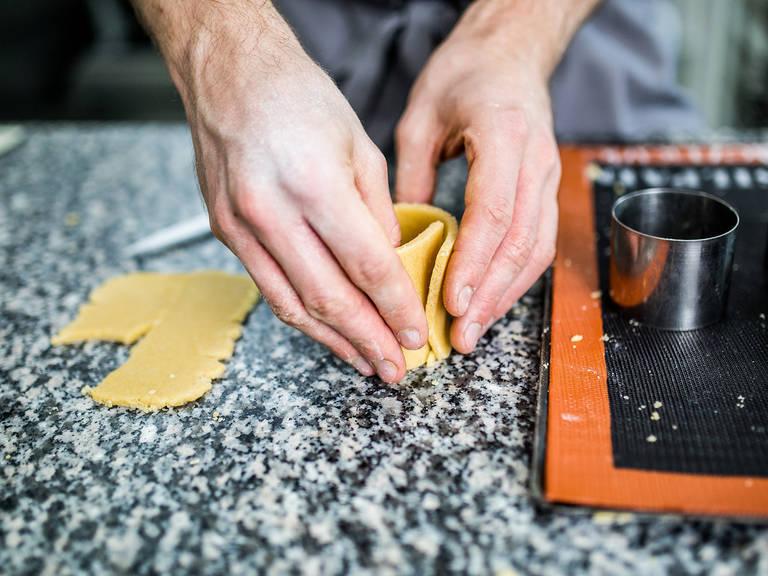 Die Dessertringe mit den Teigstreifen auslegen. Die sich überlappenden Teigschichten fest zusammendrücken, um die Ränder zu versiegeln. Für den Cup-Boden aus dem restlichen Teig Kreise in Größe der Dessertringe ausstechen. Die Teigkreise in die Ringe drücken und die Naht zwischen Boden und Wänden gut mit dem Finger verbinden.
