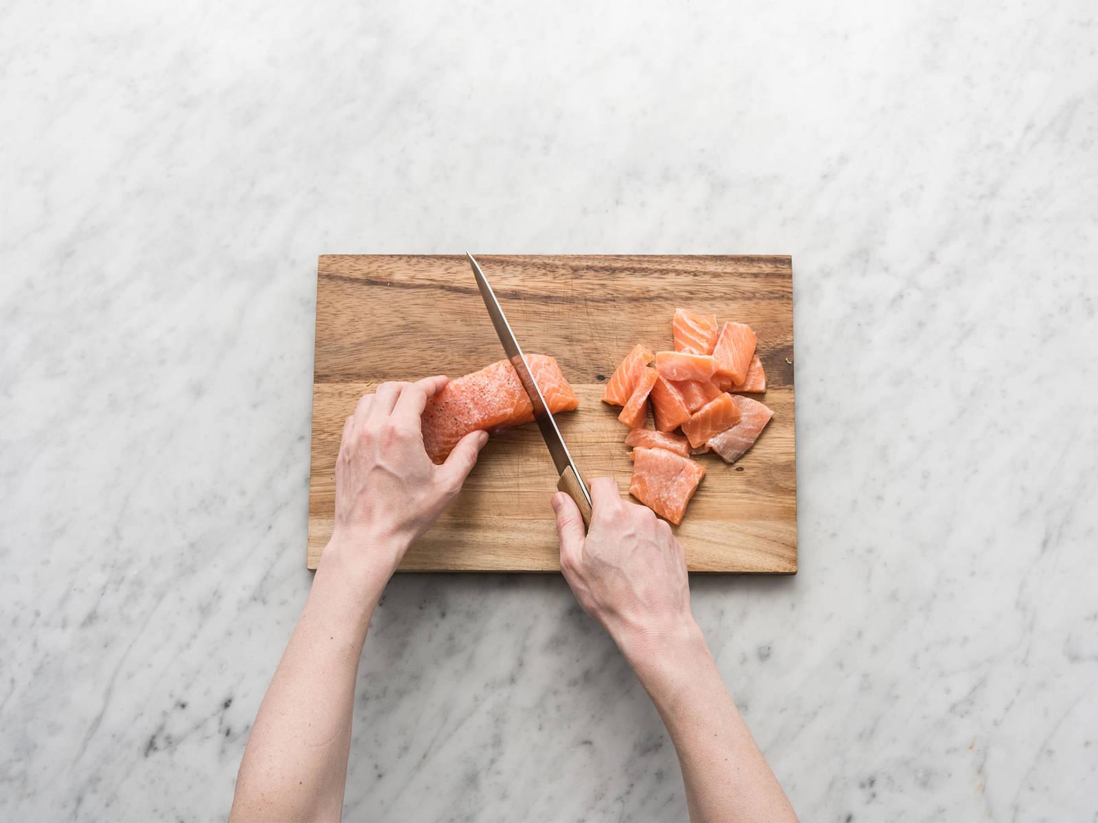 Kartoffeln in dünne Medaillons schneiden. Anschließend großen Topf mit gesalzenem Wasser füllen, aufkochen und Kartoffeln darin ca. 5 Min. blanchieren. Zitrone halbieren. Eine Hälfte auspressen und andere Hälfte in Spalten schneiden. Hälfte des Zitronensafts mit dem Lachs in einer großen Schüssel vermengen. Mit Salz und Pfeffer würzen und in mundgerechte Stücke schneiden. Dill und Kerbel fein hacken.