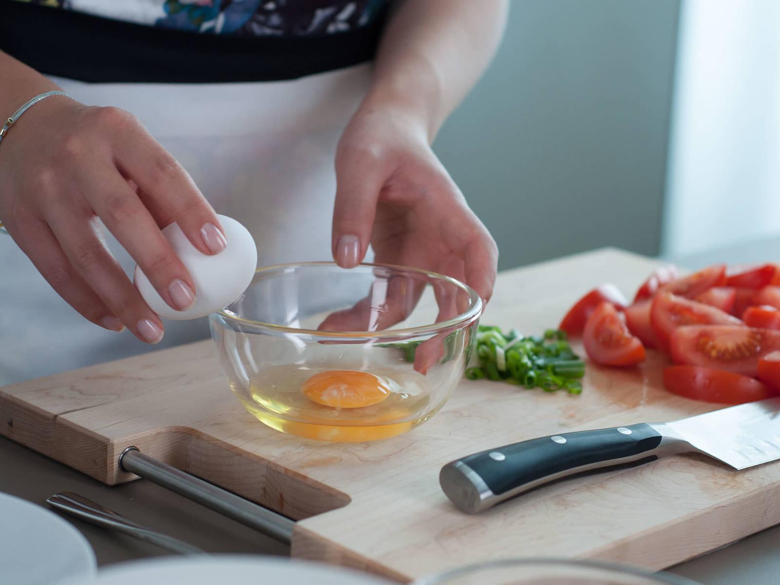 将番茄切成瓣状,小葱切圈。将鸡蛋打入小碗中。
