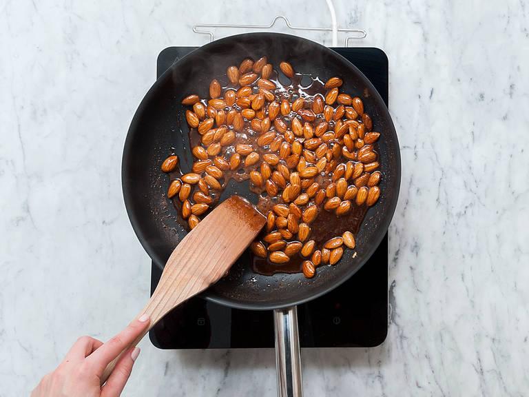 Mandeln in die Pfanne geben und vermengen, bis sie mit dem Zuckersirup ummantelt sind. Sobald das Wasser vollständig verdampft ist, die Hitze auf mittlere Stufe reduzieren und weiterrühren. Die Zuckerglasur wird nun matt und glänzt nicht mehr. Weiter rühren, bis die Mandeln beginnen zu karamellisieren und wieder glänzen. Während des Prozesses immer weiter rühren, damit die Mandeln nicht anbrennen.
