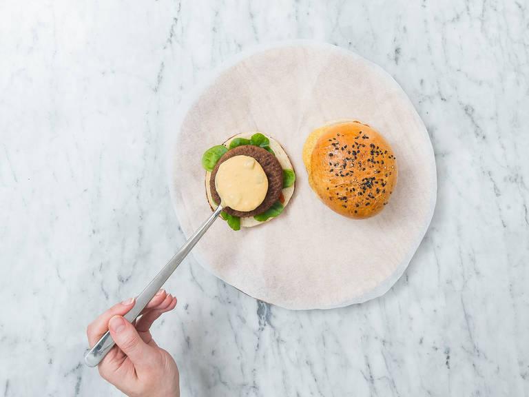 将汉堡面包横向切半,在每半上抹上辣椒酱。放入生菜、汉堡肉饼、芝士酱、玉米片、番茄片和剩余的墨西哥辣椒片。合上两半面包。尽情享用吧!
