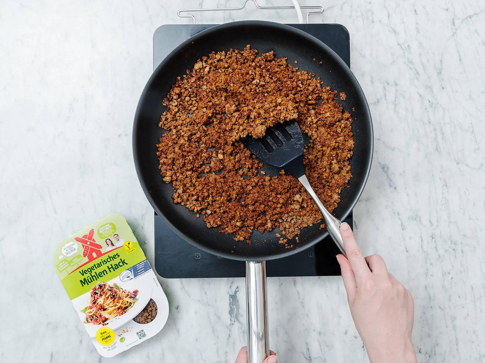 在大煎锅中热油。倒入素食肉末,翻炒4分钟。加入酱油、红辣椒和烟熏辣椒,搅拌混合。撒盐与胡椒调味。