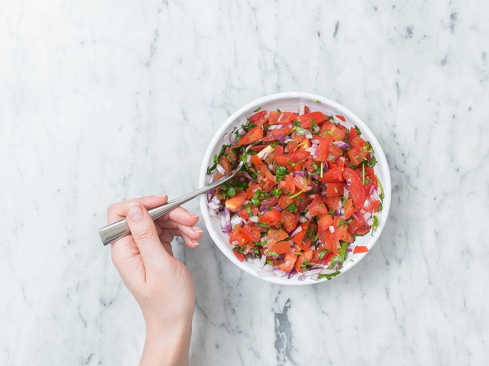 Tomaten halbieren, Strunk und Kerne entfernen und fein würfeln. Rote Zwiebel schälen und fein würfeln. Koriander fein hacken. Tomatenwürfel, Zwiebelwürfel und Koriander in einer kleinen Schüssel vermengen. Beiseitestellen.