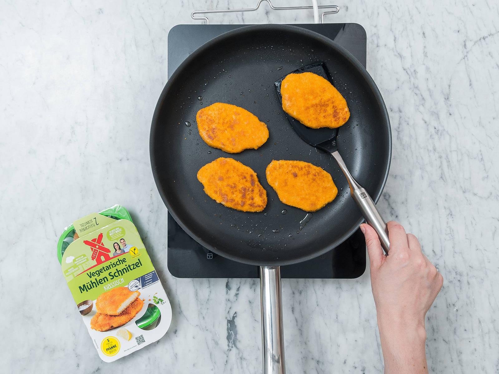 Pflanzenöl in einer großen Pfanne bei mittlerer Hitze erwärmen. Vegetarische Schnitzel von jeder Seite ca. 2 - 3 Min. anbraten. Aus der Pfanne nehmen und ca. 1 - 2 Min. abkühlen lassen. Anschließend in Streifen schneiden.