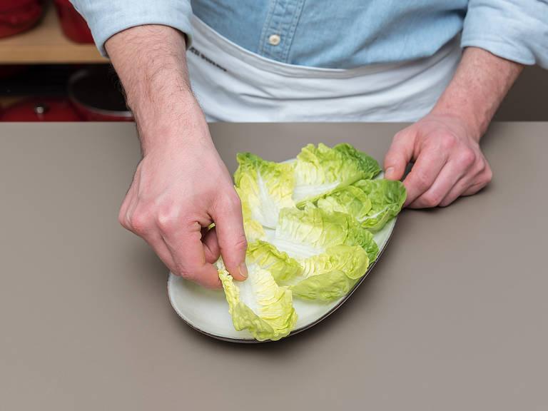 将罗马生菜的叶片摘下,一次一片,然后清洗干净,甩掉多余水分。将生菜叶放到一个盘子中,展开的一面朝上。