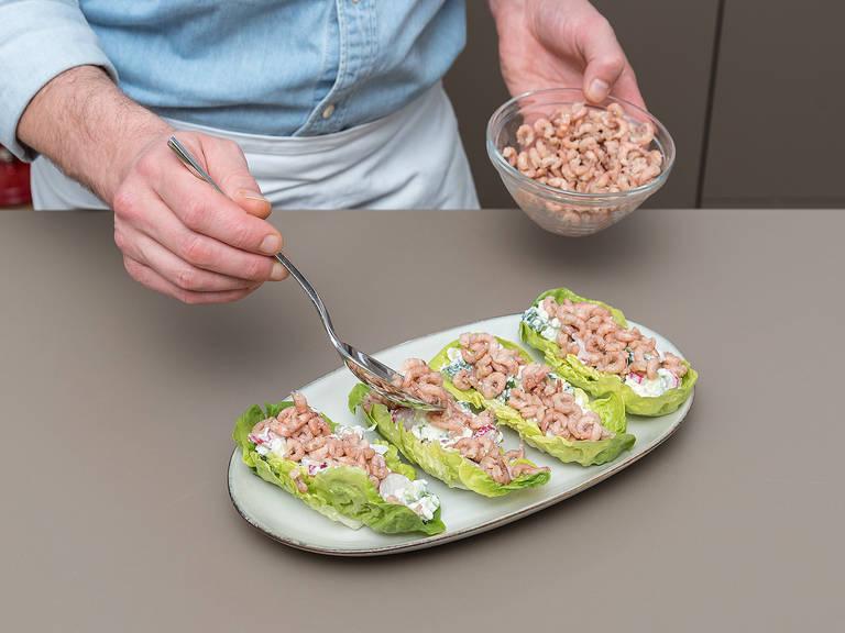 在生菜叶中放上黄瓜芝士混合物,再放上些许海虾。
