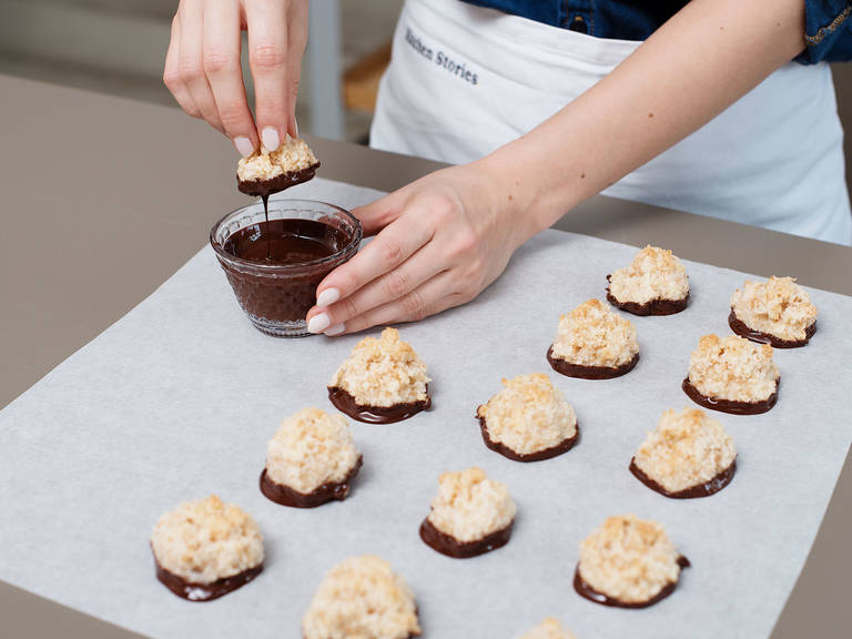 Break up chocolate and melt in a heatproof bowl set over a pot of simmering water. Carefully remove macaroons from baking paper and partially dip in chocolate. Place on parchment paper to dry for approx. 1 hr., then enjoy!