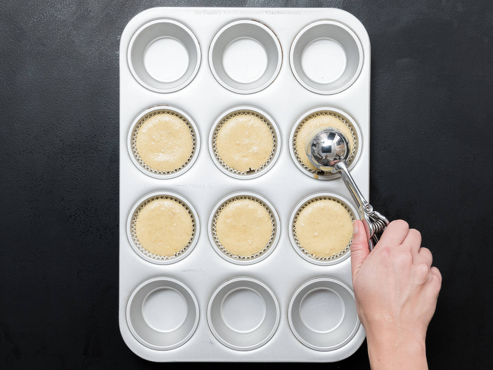 In another bowl, mix butter, sugar, and vanilla sugar. Add egg, oil, and rum extract to the mixture and beat to combine. Alternately add flour mixture and milk to the butter mixture and stir until dough is combined. Stir in nuts. Line muffin tin, and fill each mold up to ¾ with batter. Bake at 180ºC/350ºF for approx. 20 min., until golden brown. Remove from oven and set aside to cool.