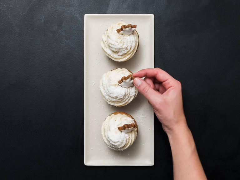 与此同时,制作糖霜:将黄油拌匀。一次一点地加入糖粉,充分混合。放入香草糖和奶油,搅打发泡。然后倒入裱花袋中,挤到纸杯蛋糕上,然后撒上椰蓉。饰以肉桂星星。尽情享用吧!