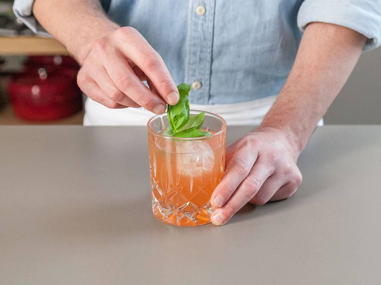 Add some grenadine syrup, gin, passionfruit nectar, and crushed ice in a cocktail shaker. Shake vigorously. Pour the cocktail mixture into a glass, top with ginger ale, and garnish with basil. Enjoy!