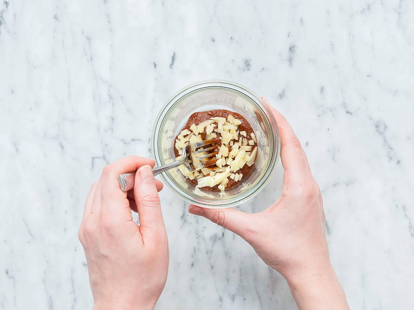Karotte schälen und reiben. Frühlingszwiebel in Ringe schneiden. Tofu würfeln. Öl in einer Pfanne erwärmen und Tofuwürfel ca. 5 Minuten anbraten. Für die Würzpaste Knoblauch und Ingwer schälen und fein hacken. Misopaste, Tahini, rote Currypaste, Sojasauce, Sesamöl und gehackten Knoblauch und Ingwer in ein verschließbares Glas geben und verrühren.