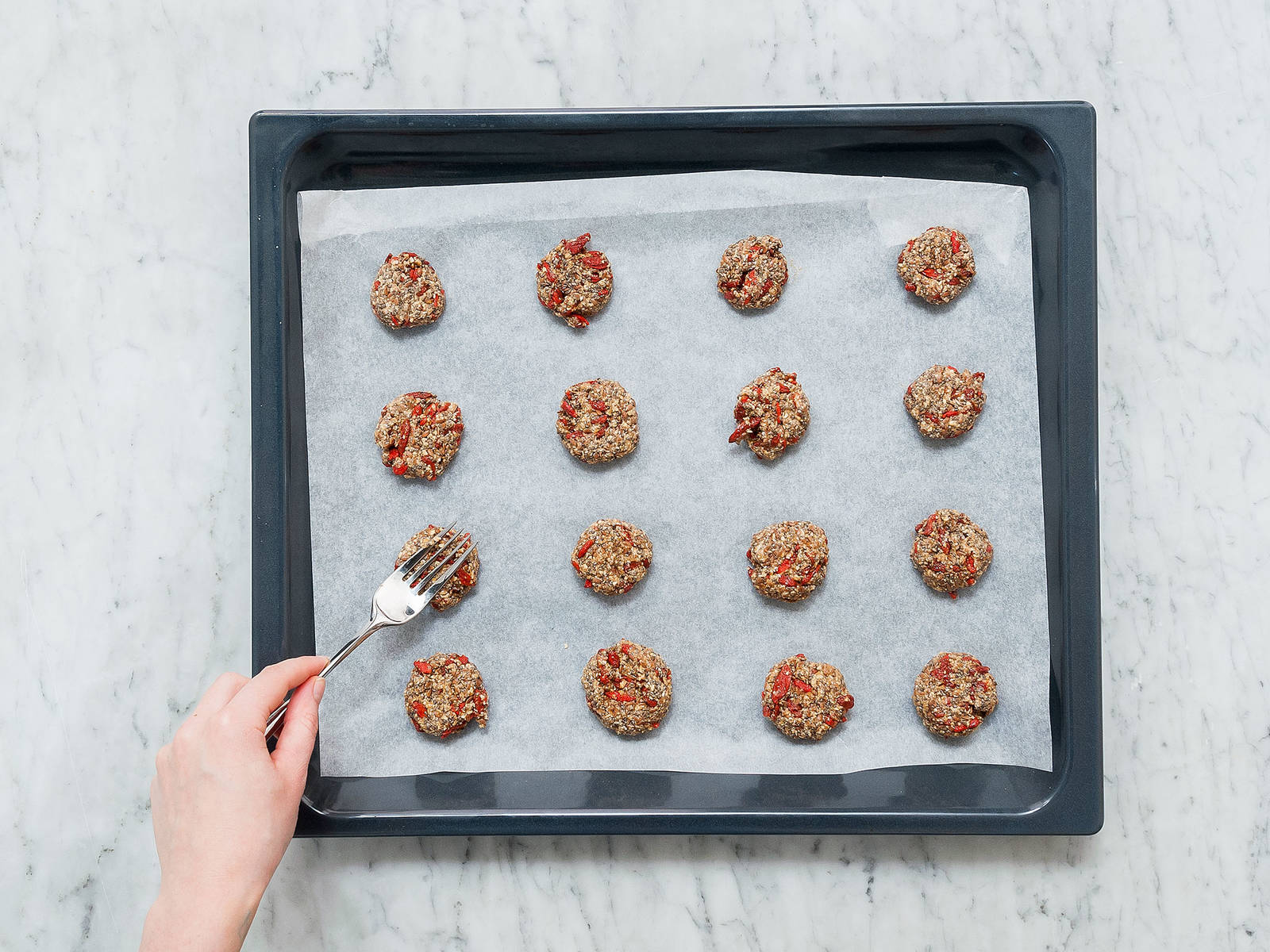 Slightly wet your hands with water. Portion the dough with a teaspoon and roll it with your hands to form small balls. Add to a parchment-lined baking sheet and gently flatten with a fork. Bake at 180°C/350°F on the middle rack for approx. 8 – 10 min. Remove from oven and let cool.