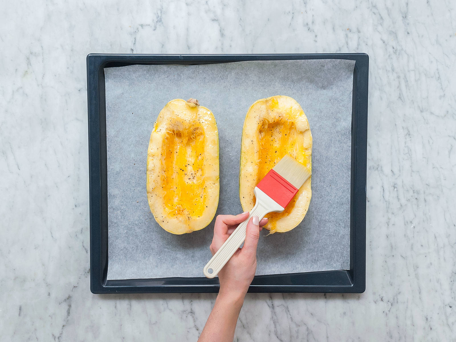Pre-heat oven to 200°C/390°F. Halve spaghetti squash lengthwise and remove the core with a spoon. Transfer squash to a parchment-lined baking sheet. Brush with olive oil and season with salt and pepper. Bake for approx. 40 min.