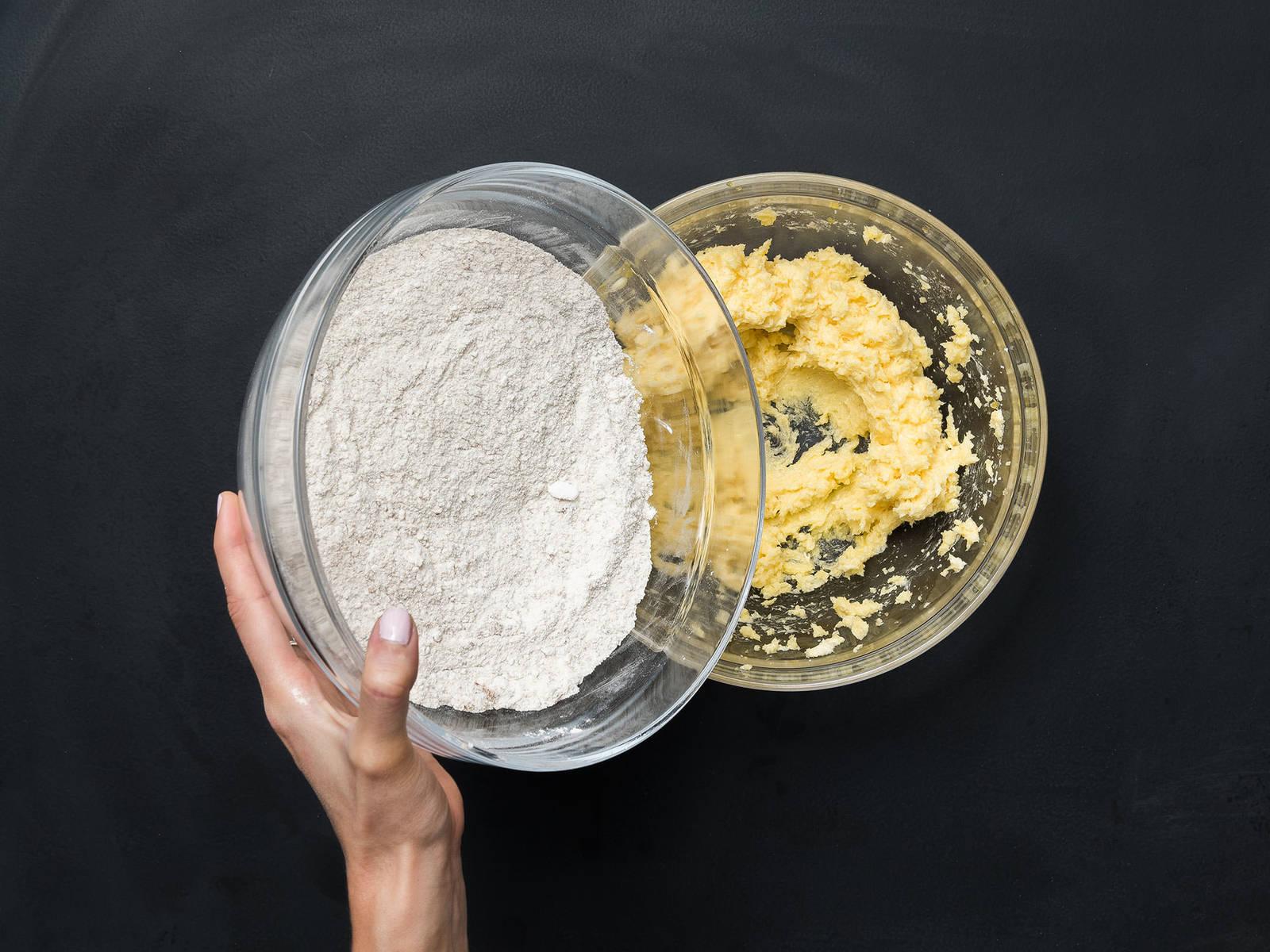 将烤箱预热至180℃。在大搅拌碗中搅打混合黄油、糖、香草糖、盐、蛋黄和香草精。在另一个大碗中,混合面粉、淀粉和杏仁粉,分次倒入黄油鸡蛋混合物,直至揉成一个柔滑面团。