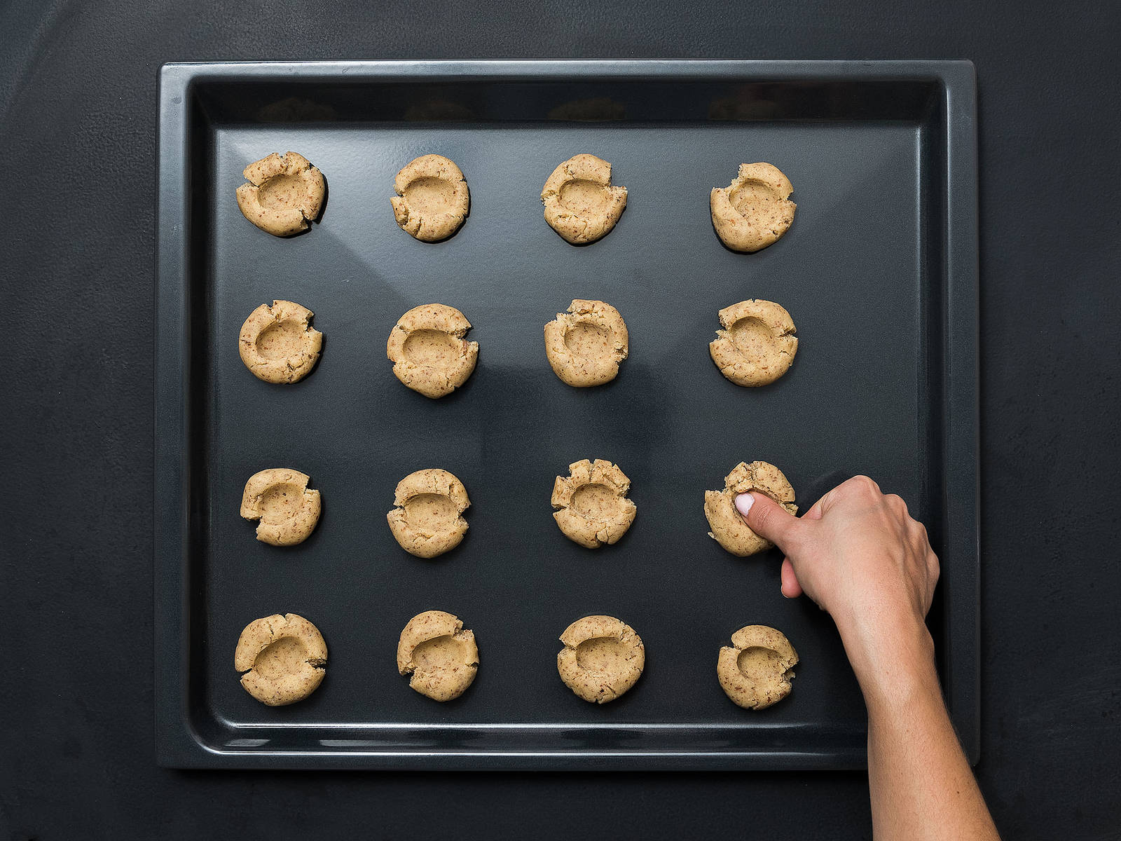 Split the dough into balls the size of a large walnut and place on a lined baking sheet. Lightly flatten the balls and, using the end of a cooking spoon or your thumb, create a small well in the center of each cookie.