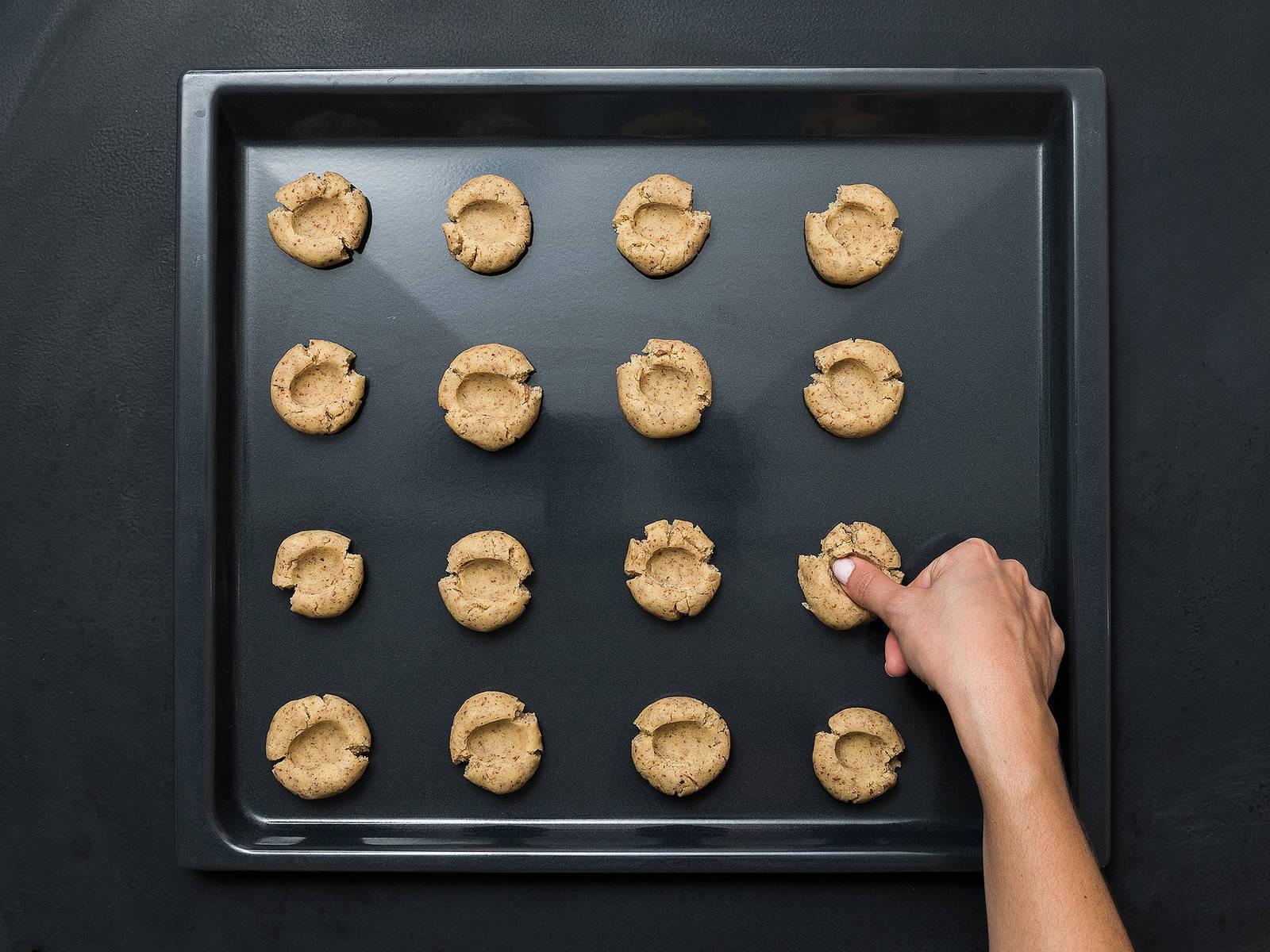 将面团分成多个核桃大小的小球,放到铺好烘焙纸的烤盘上。稍微压平面球,用料理勺底部或拇指,在每个曲奇顶部中间做出一个小漩涡花纹。