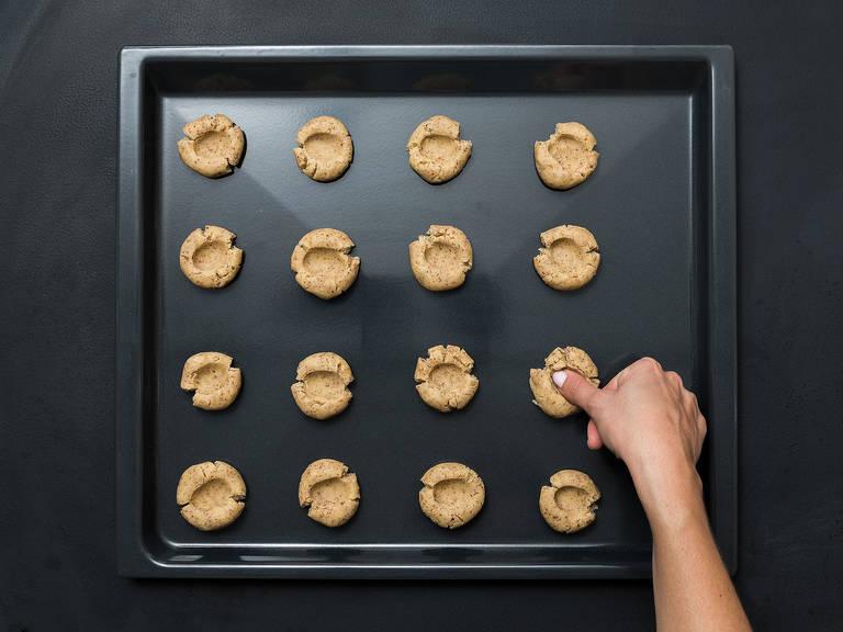 Den Teig zu walnussgroßen Bällchen formen und diese auf ein mit Backpapier ausgelegtes Backblech legen. Leicht flach drücken und mit dem Kochlöffelstiel oder dem Daumen kleine Vertiefungen in die Mitte der Teigbällchen drücken.