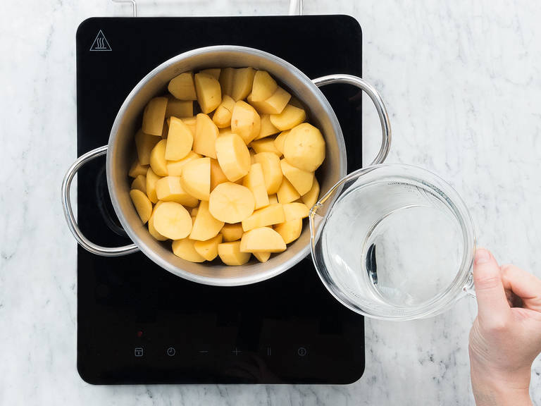 Preheat oven to 200°C/390°F. Wash and slice leek, then set aside. Peel potatoes and cut into bite-sized pieces. Add cut potatoes to a large pot and fill up with water until they are covered. Salt water, then bring to a boil. Reduce the heat and cook for approx. 10 min. over medium heat.