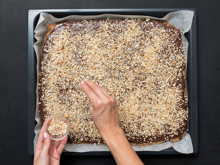 Spread melted chocolate over the cooled bars. Sprinkle the chopped nuts on top. Leave to dry for approx. 30 min. and cut into rectangles for serving. Enjoy!