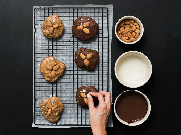Chop up the couverture and melt in a heatproof bowl set over a pot of simmering water. In a small bowl, mix confectioner's sugar, water, and lemon juice to make a light glaze. Dip gingerbread cookies in icing or chocolate as desired and garnish with whole almonds. Place on rack to set and enjoy!