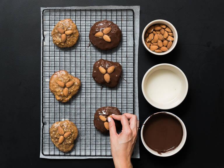 Die Schokolade grob hacken und in eine hitzebeständige Schüssel geben. Diese über einen Topf mit köchelndem Wasser stellen. Die Schokolade unter Rühren schmelzen lassen. In einer kleinen Schüssel Puderzucker, Wasser und Zitronensaft zu einer Glasur verrühren. Nach Belieben die Elisenlebkuchen in die Zucker- oder Schokoladenglasur tunken. Ganze Mandeln darauf verteilen und trocknen lassen. Guten Appetit!