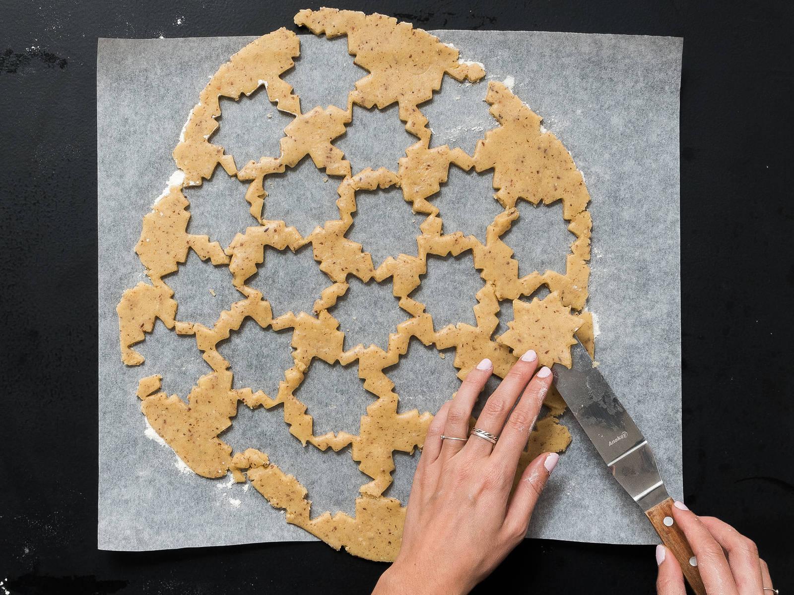 将烤箱预热至180℃。在工作台上撒些面粉,将面团擀成2毫米厚。用饼干模具切出曲奇形状,放到铺好烘焙纸的烤盘上。在半份面皮的中间用小的圆形模具切出一个小圆孔。放到烤箱中,以180℃烤15分钟,或直至烤成金棕色。从烤箱中取出,放凉。