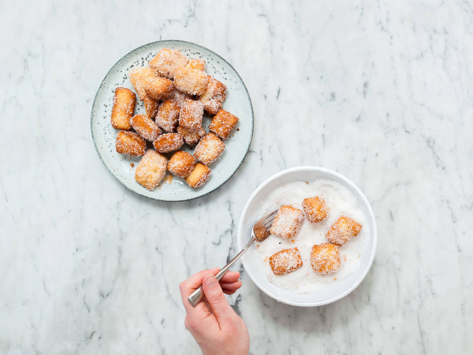 Transfer sugar onto a plate and roll deep-fried dough bites in it while they are still warm. Toss to coat. Repeat until all dough bites are completely sugar coated. Enjoy!