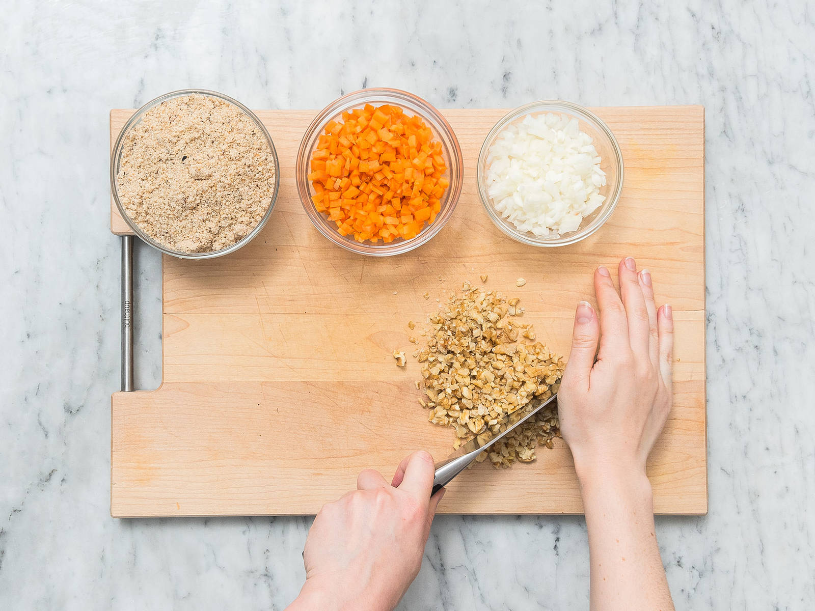 Preheat oven to 190°C/375°F. Grease loaf pan and dust with breadcrumbs. Peel and finely dice some of  the onions and carrot. Finely chop walnuts. Crumble white bread. Add ground flaxseed and water to a small bowl and stir to combine.