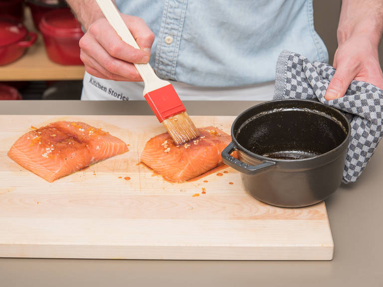Drizzle salmon fillets with half of the remaining olive oil, sprinkle with blood orange zest and remaining garlic, and season with salt and pepper. Brush fillets well with some of the blood orange syrup.